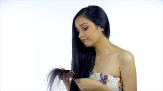 Attractive young girl with long hair is sad about her hair damage - haircare concept