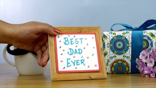 Indian girl hands placing a wooden frame with the inscription of Best Dad Ever
