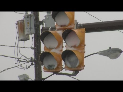 LED traffic lights clogged with snow as people run red lights