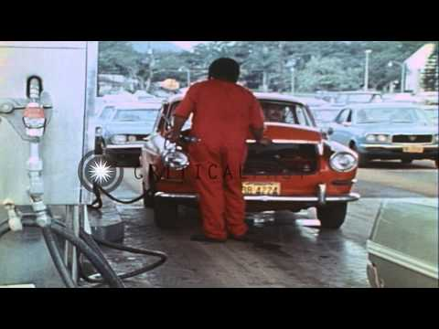 Service station worker directs traffic as vehicles line up at PX gas station due ...HD Stock Footage