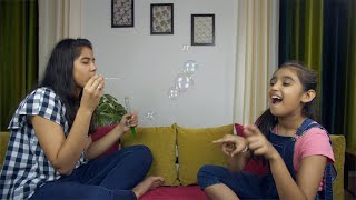 Young cute siblings playing together with soap bubbles while sitting on a couch