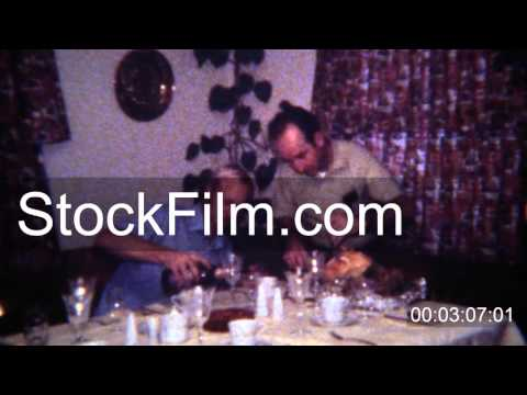 1971: Gay men couple carving turkey pouring wine for holiday celebration. BOULDER. COLORADO