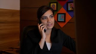 Young Indian woman picking up the phone while working in office