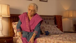Indian lady reads a book with glasses while sitting in bed - the lifestyle of old people