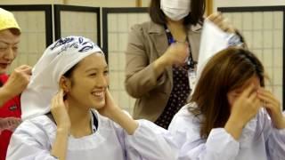 外国人に昔ながらのかっぽう着と手ぬぐい頭巾をかぶせて料理教室の始ま...