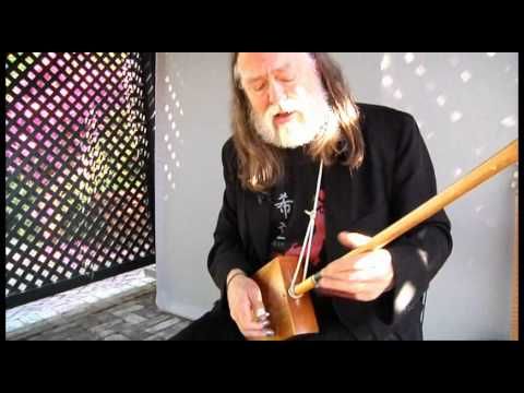 Scott Ainslie plays cigar box guitar at the Ships of the Sea Museum
