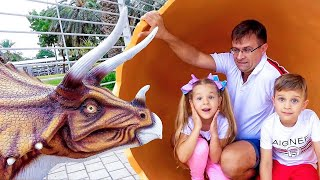 Diana y Roma caminan por el parque de dinosaurios
