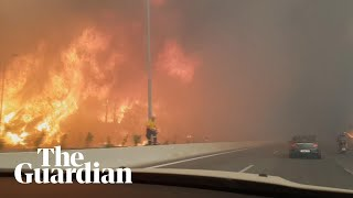 Car drives through wildfires on motorway near Athens