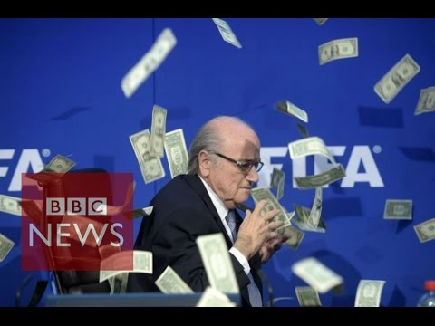 Moment Sepp Blatter was showered with fake dollar bills - BBC News