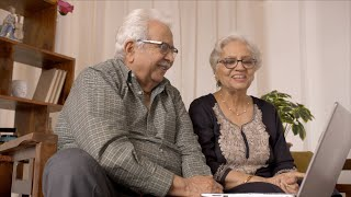 Happy Indian grandparents doing a video chat using laptop with their family