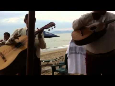 6 piece mariachi band play a romantic song on the beach in