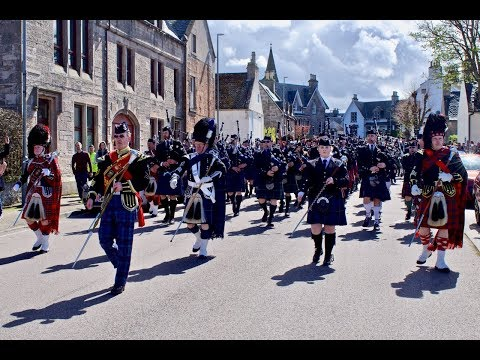 Massed pipes and drums march through Nairn in Scottish highlands for Charity, April 2018