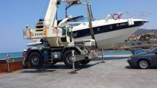 Genio con gru terex gigante come escavatore scarica barca yacht. Santa maria di castellabate
