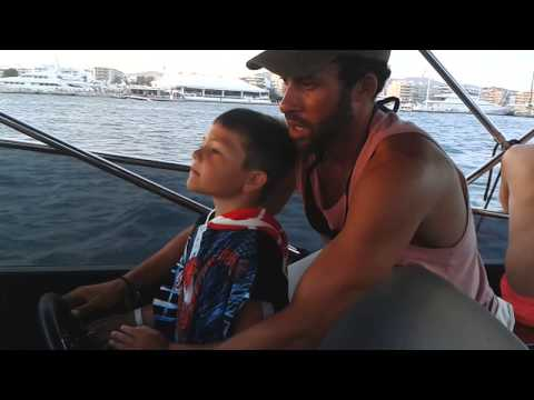 William drives the boat with Jonny in Ibiza