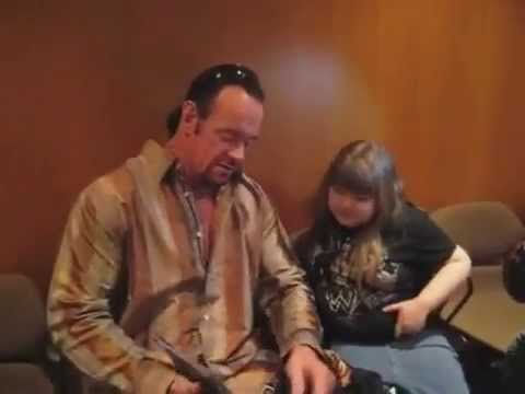 The Undertaker from the WWE breaks character and greets a young fan.