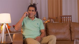 40 year old man having a phone call - Indian male sitting on the sofa