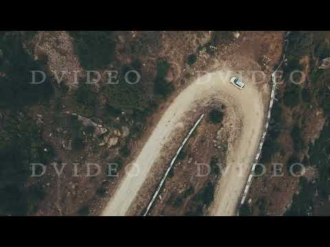 Aerial view white car jeep moving along winding road mountain at summer day