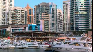 View of Dubai Marina Towers reflected in water of canal in Dubai day to night timelapse