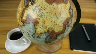 Closeup shot of male's hand exploring a globe with the help of a magnifying glass