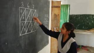 विद्यालय की कक्षा-5 की छात्रा कक्षा-4 के बच्चों को गुणनफल की नई तकनीक सिखाती हुई।