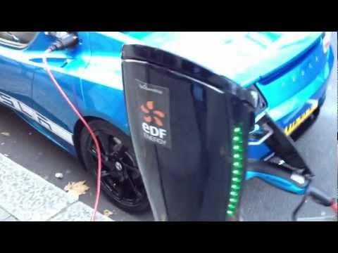 Shiny blue Tesla Roadster at electric vehicle charging point in London