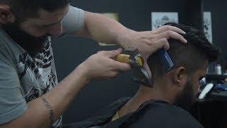 Парикмахер Аммар Калш стрижет посетителей  с помощью топора