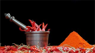 Pan shot of dried red chilies (lal mirch - Indian spice), chili powder, mortar and pestle