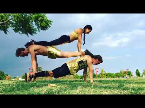 Three People Perform Stacked Team Push Up - 986716