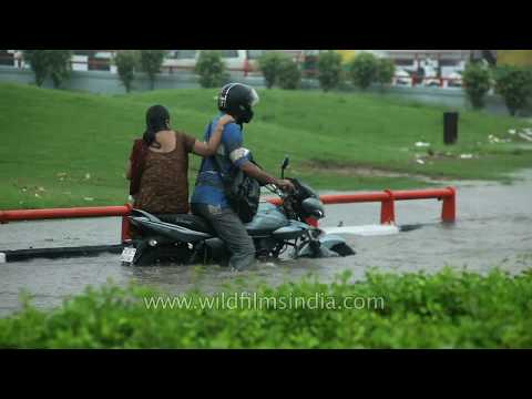 Man tries to drive through flooded water on bike but fails, Delhi
