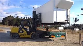 大型フォークリフトでトラックにコンテナ積み込み