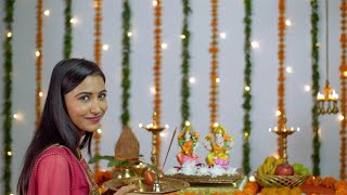 A young attractive woman in front of Lord Ganesha and Goddess Lakshmi On Diwali