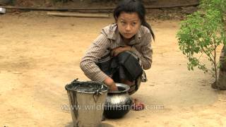 Manipuri woman swabs floor with cow dung