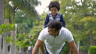 Smiling father and young son spending the weekend together in a park - leisure concept