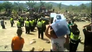 Colombianos cantan el Himno Nacional mientras cruzan el rió Tachira en Venezuela.