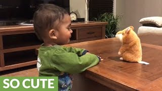 Baby has conversation with repeating hamster toy