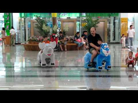 Children Riding Electric Animals at a Mall in Beijing, China