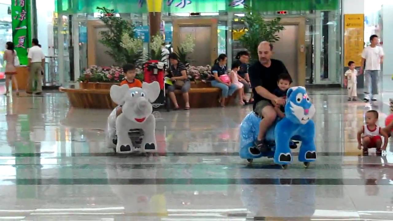 Children Riding Electric Animals At A Mall In Beijing