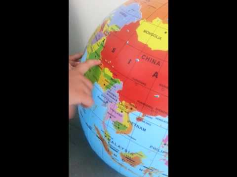 2 year old showing countries in globe in an alphab