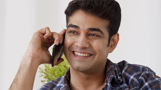 Young handsome Indian man happily talking on the phone