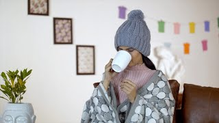 Closeup shot of an Indian woman enjoying a cup of coffee during the winter season