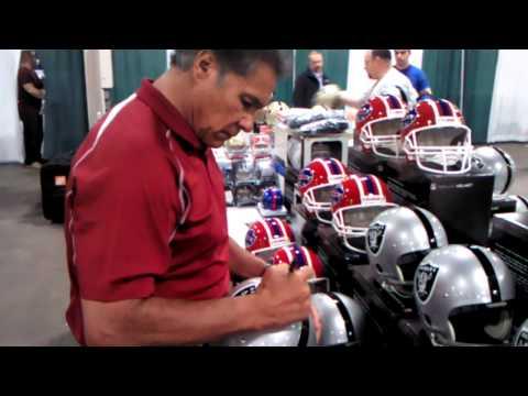 Jim Plunkett signing helmets for Phg Sports