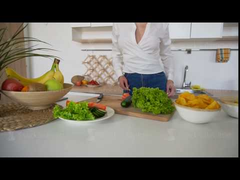 Slender blonde woman completes preparation of healthy breakfast and spreads vegetables, standing at