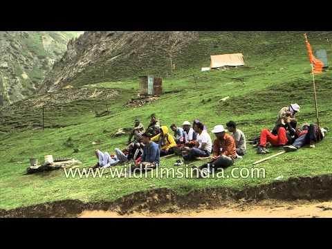 Tired pilgrims sleep in a grassy meadow, en route Amarnath