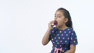 Attractive Indian kid cutely eating a juicy plum in trendy casual wear - slow motion shot