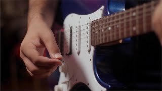 Closeup shot of a boy playing electrical guitar