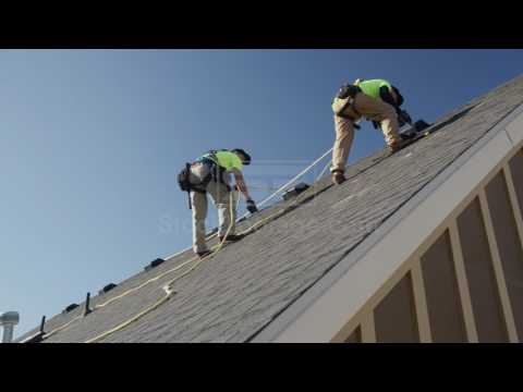 Wide panning low angle shot of workers drilling on roof