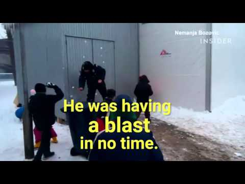 Refugee children and police have a snowball fight.