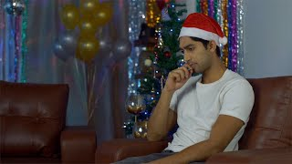 Lonely Indian guy in Santa hat celebrating Christmas at home on Christmas Eve in India