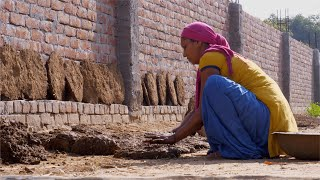 A woman flattening the cow dung cake for cooking fuel in rural India