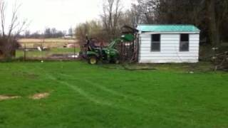 John Deere tractor drives into shed